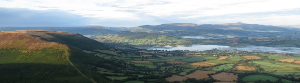 Wider view of Llangorse Lake and the Brecons, taking in Mynydd Llangorse on the left. There's a great 12-mile circular walk taking in the lake, the low hill behind the lake (Allt) and Mynydd Llangorse.